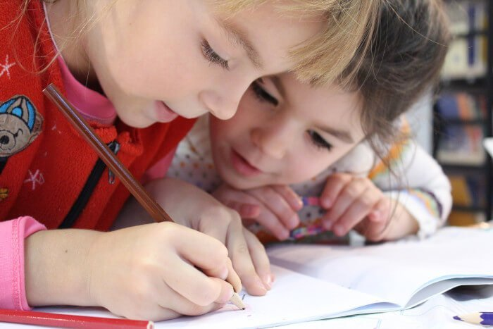 two young students working closely in book
